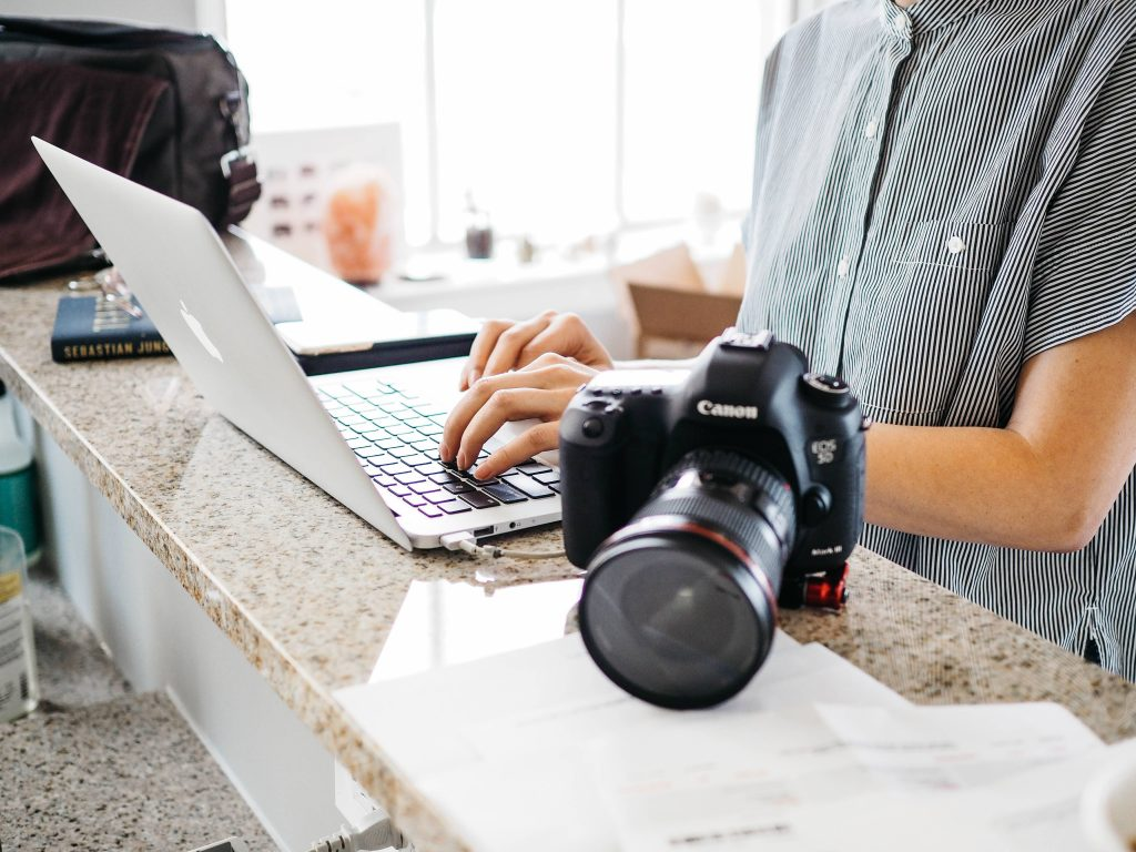Camera next to a man typing on a MacBook Pro