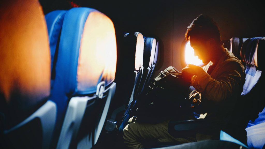 Man sitting on plane as sun comes up
